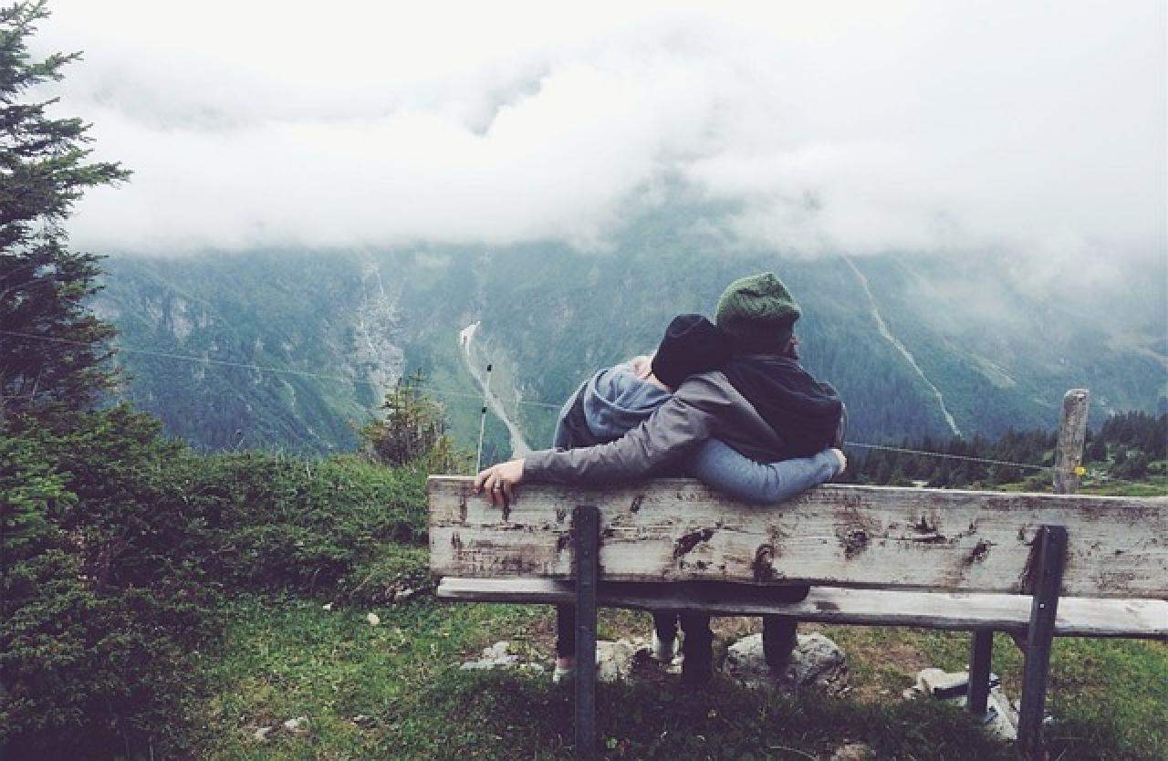 Una pareja mirando el frió paisaje en la cima de una montaña